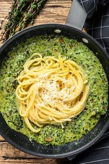 Spaghetti-nudeln mit spinat in sahnesauce mit parmesan in einer pfanne
