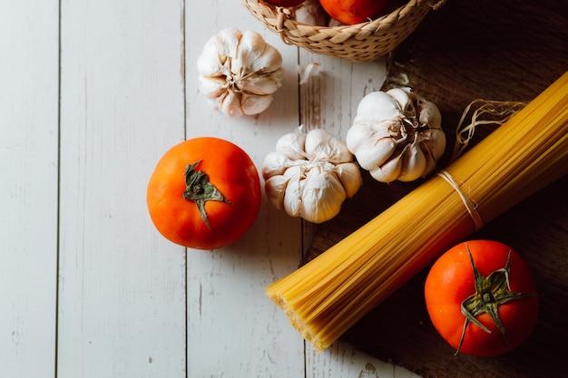 Spaghetti-nudeln mit tomaten und knoblauch auf weißem hintergrund aus holz.