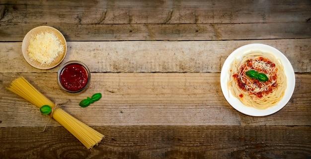 Spaghetti-nudeln mit tomatensauce, käse und basilikum auf holztisch. traditionelles italienisches essen. banner. draufsicht flat lay.