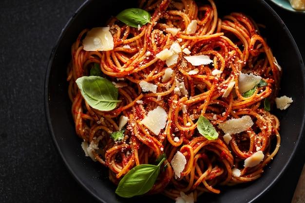 Spaghetti-nudeln mit tomatensauce, käse und basilikum in einer schüssel serviert