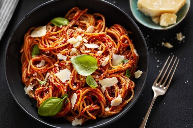 Spaghetti-nudeln mit tomatensauce, käse und basilikum in einer schüssel serviert.