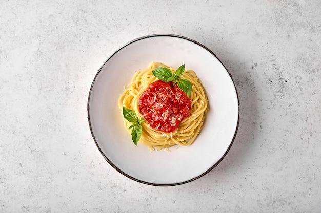 Spaghetti-nudeln von oben in tomatensauce, parmesan und basilikum auf weißem teller auf licht