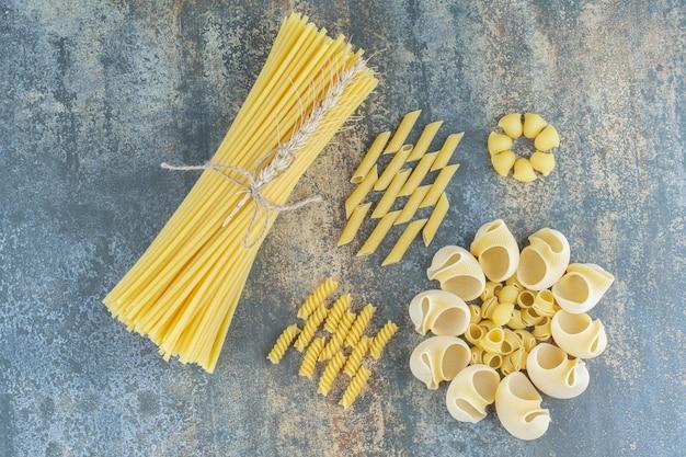 Spaghetti, penne, fusilli und gestapelte nudeln auf dem marmorhintergrund.