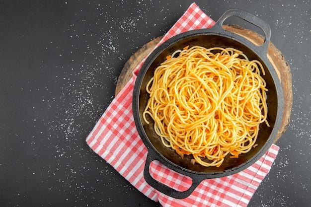 Spaghetti-pfanne mit draufsicht auf holzbrett auf dunklem hintergrund