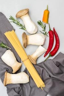 Spaghetti-pilze und graue serviette mit rotem chili auf dem tisch