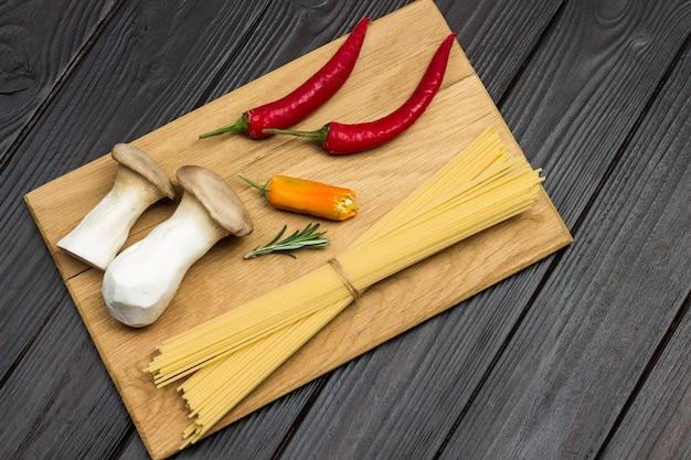Spaghetti-pilze und roter chili auf schneidebrett