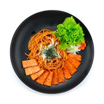 Spaghetti samyang spicy sauce mit spam-schinken auf zwiebelkotelett und algen korean food fusion style mit geschnitztem gemüse-draufsicht dekorieren