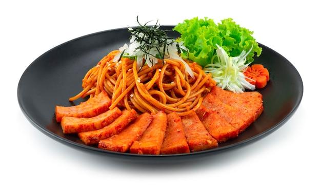 Spaghetti samyang spicy sauce mit spam-schinken auf zwiebelkotelett und algen korean food fusion style mit geschnitzter gemüse-seitenansicht dekorieren