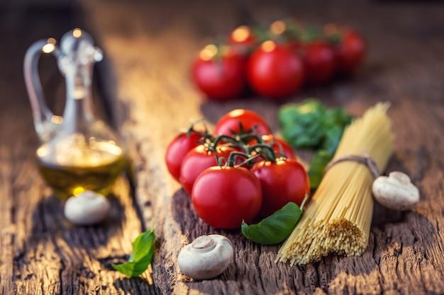 Spaghetti tomaten basilikum olivenöl parmesan und champignons auf eichenbrett