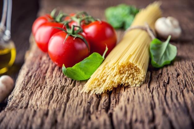 Spaghetti tomaten basilikum olivenöl parmesan und champignons auf sehr altem eichenbrett
