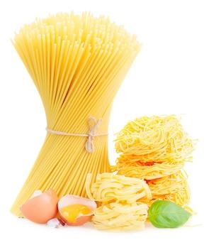 Spaghetti, tonarelli und tagliatelle nudeln mit rohem ei auf weiß