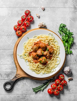 Spaghetti und fleischbällchen auf einem teller mit tomaten, kräutern und knoblauch. auf hölzernem hintergrund