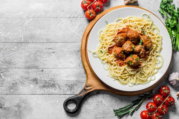 Spaghetti und fleischbällchen auf einem teller mit tomaten, kräutern und knoblauch