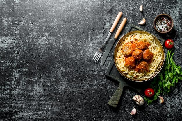 Spaghetti und fleischbällchen in einer pfanne mit gewürzen, kräutern und tomaten. auf rustikalem hintergrund