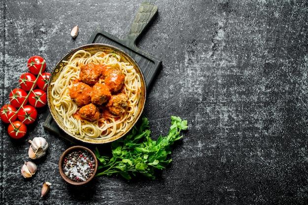 Spaghetti und fleischbällchen in einer pfanne mit petersilie, tomaten und knoblauch. auf schwarzem rustikalem hintergrund