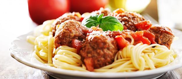 Spaghetti und fleischbällchen mit basilikumgarnitur