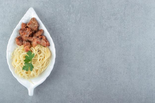 Spaghetti und mariniertes hühnchen auf einem blattförmigen teller.