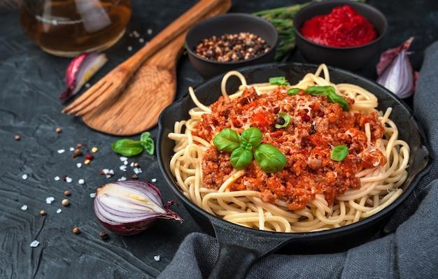 Spaghetti und sauce in einer pfanne werden mit käse und frischem basilikum auf einem hintergrund von bestreut