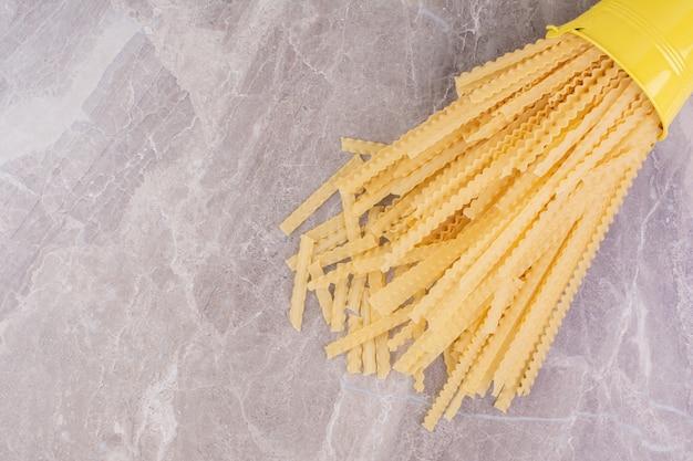 Spaghetties aus einem gelben metalleimer.
