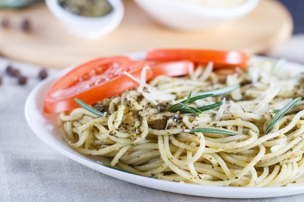Spaghettinudeln mit pestosoße, tomaten und käse auf einer leinentischdecke.