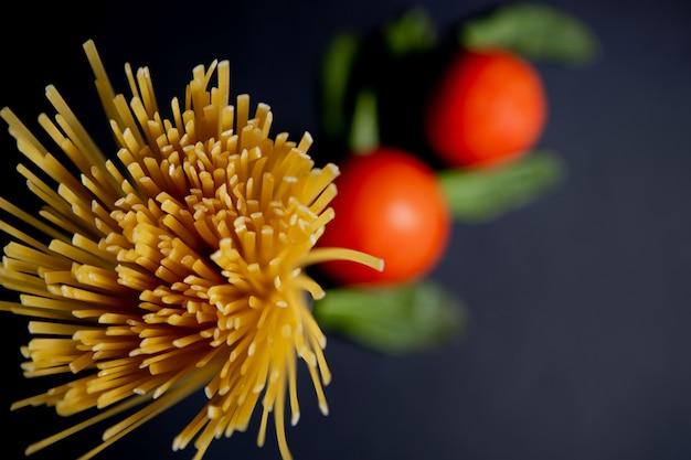 Spaghettipaste, tomate und andere produkte zum kochen auf dunklem hintergrund draufsicht. platz für text, draufsicht