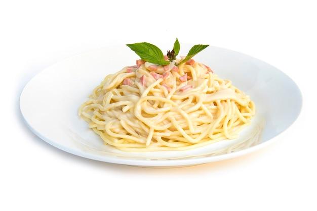 Spaghettis carbonara zwiebel und champignoncremesoße mit der seitenansicht der traditionellen italienischen küche des schinkens und des frischen basilikums lokalisiert
