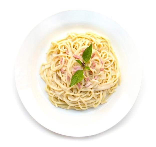 Spaghettis carbonara zwiebel- und pilzcremesoße mit der draufsicht der traditionellen italienischen kücheart des schinkens und des frischen basilikums lokalisiert