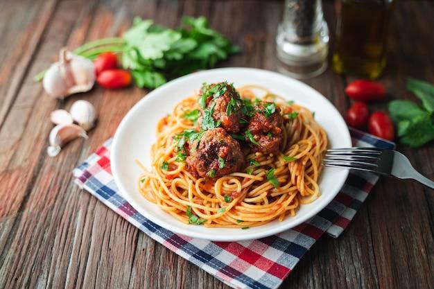 Spaghettis und fleischklöschen mit tomatensauce im weißen teller auf hölzernem rustikalem brett