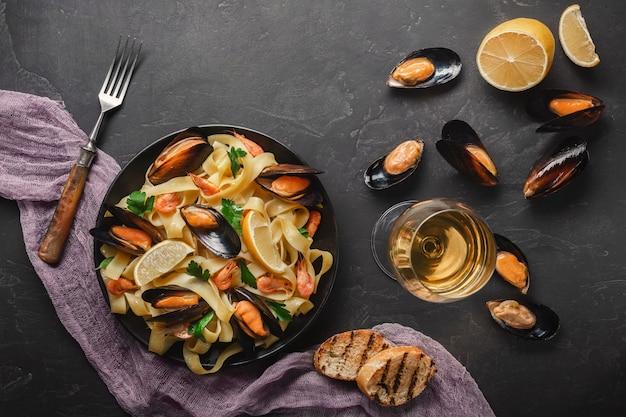 Spaghettis vongole, italienische meeresfrüchteteigwaren mit muscheln und miesmuscheln, in der platte mit kräutern und im glas weißwein auf rustikalem steinhintergrund.
