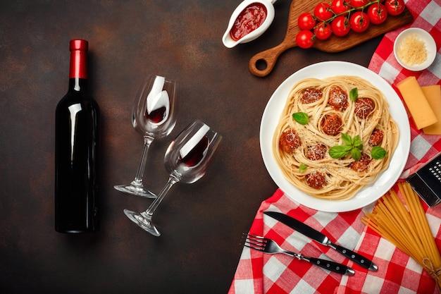 Spaghettiteigwaren mit fleischklöschen, kirschtomatensauce, käse, weinglas und flasche auf rostigem hintergrund.