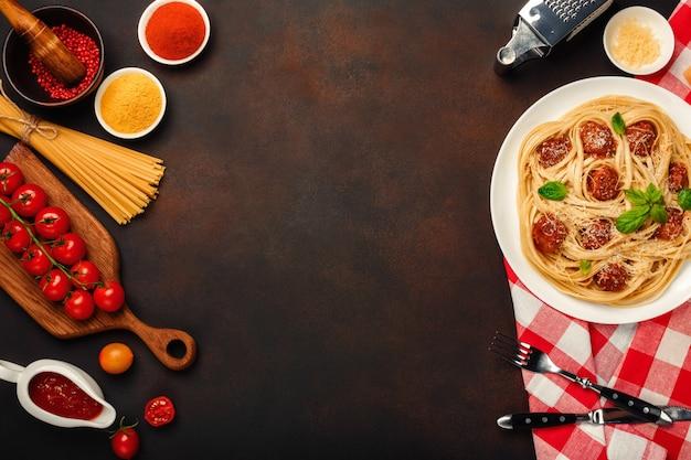 Spaghettiteigwaren mit fleischklöschen, kirschtomatensauce und käse auf rostigem hintergrund.