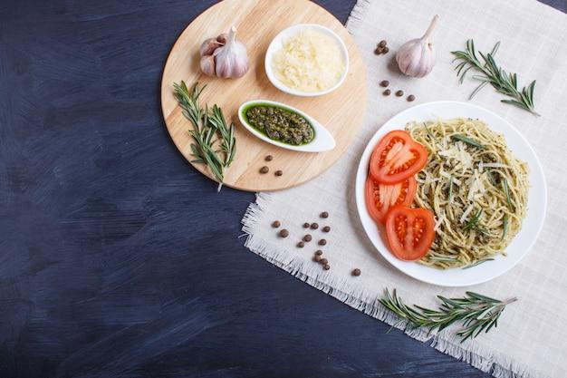 Spaghettiteigwaren mit pestosoße, tomaten und käse auf einer leinentischdecke auf schwarzem hölzernem hintergrund.