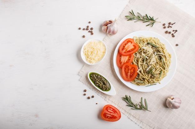 Spaghettiteigwaren mit pestosoße, tomaten und käse auf einer leinentischdecke auf weißem hölzernem hintergrund.