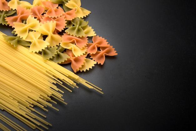Spaghettiteigwaren und farfalle-teigwaren auf schwarzer küchenarbeitsplatte