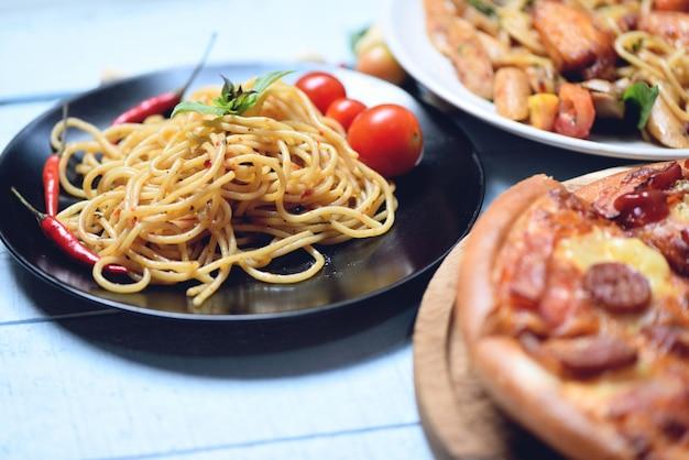 Spaghettiteigwaren und -pizza auf italienischem lebensmittelspaghettis bewohner von bolognese des hölzernen behälters auf platte