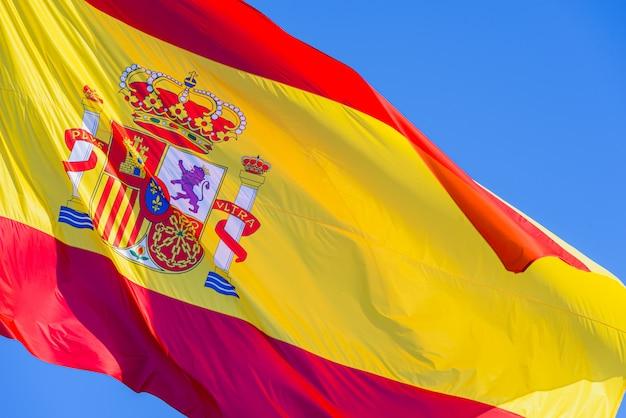 Spanien-flagge mit dem königlichen schild, das in den wind auf hintergrund des blauen himmels wellenartig bewegt