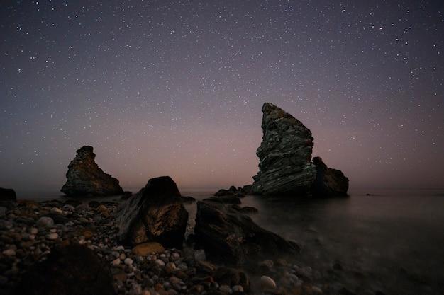Spanien, malaga, nerja, molino de papel: sternennacht am strand mit felsen