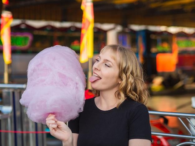 Spanische blonde frau isst süße zuckerwatte im vergnügungspark