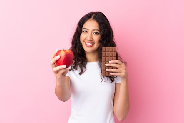 Spanische chinesin über der lokalisierten rosa wand, die eine schokoladentablette in einer hand und einen apfel in der anderen nimmt