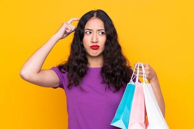 Spanische chinesische frau mit der einkaufstasche, die zweifel hat und mit verwirren gesichtsausdruck