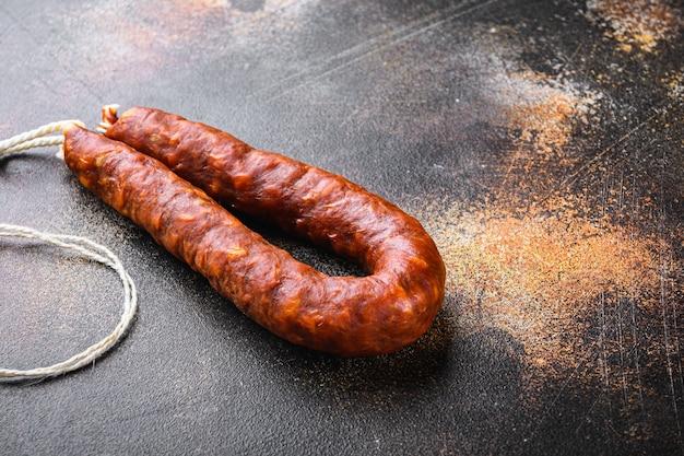 Spanische chorizo-salami-wurst auf dunklem hintergrund.