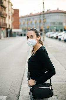 Spanische frau, die gesichtsschutzmaske auf der straße trägt. coronavirus-lebensstil