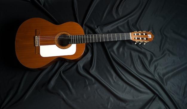 Spanische gitarre auf schwarzem hintergrund