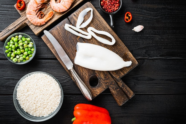 Spanische meeresfrüchte-paella-zutaten, reis, garnelen, muscheln, erbsen über schwarzem holztisch, flach mit kopierraum