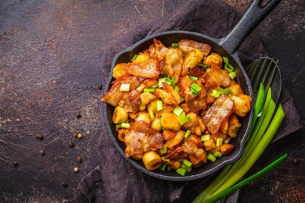 Spanische migas mit schweinefleisch und frühlingszwiebeln in gusseisenpfanne auf dunklem hintergrund.