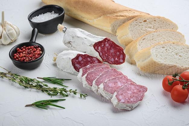 Spanische salcichon-scheiben mit panini und kräutern auf weißer oberfläche.
