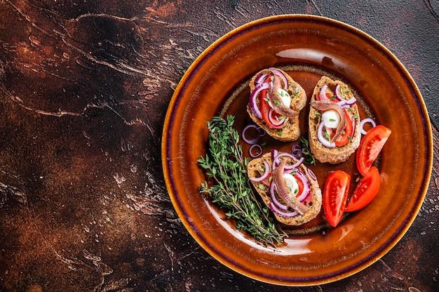 Spanische tapas auf brot mit olivenöl, kräutern, tomaten und würzigen sardellenfilets. dunkler hintergrund. ansicht von oben. platz kopieren.