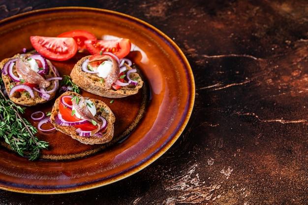 Spanische tapas auf brot mit olivenöl, kräutern, tomaten und würzigen sardellenfilets
