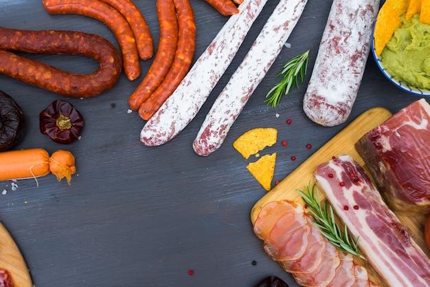 Spanische tapas mit salami, chorizo, lomo, jamon mit scharfer salsa-sauce und oliven, picknicktisch