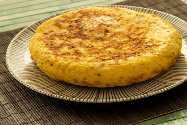 Spanische tortilla auf einem rustikalen teller und einer holztischdecke